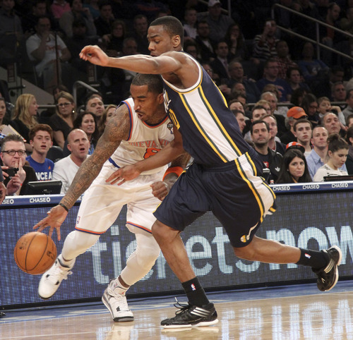 New York Knicks' J.R. Smith (8) drives past Utah Jazz's Marvin Williams during the second half of the NBA basketball game, Saturday, March 9, 2013, at Madison Square Garden in New York. The Knicks won 113-84. (AP Photo/Mary Altaffer)