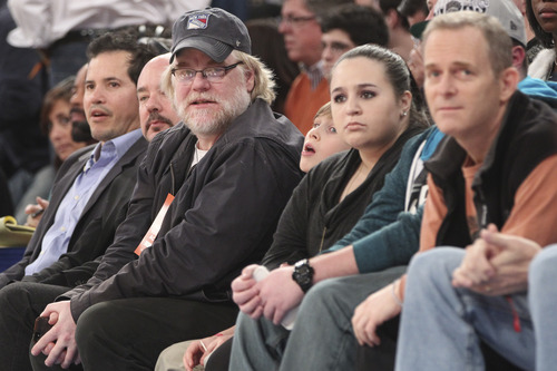Actors John Leguizamo, left, and Philip Seymour Hoffman, third from left, watch the first half of an NBA basketball game between the New York Knicks and the Utah Jazz, Saturday, March 9, 2013, at Madison Square Garden in New York.  (AP Photo/Mary Altaffer)