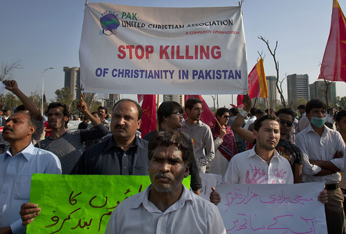 Pakistani Christians hold posters during a demonstration demanding that the government rebuild their homes after they were burned down following an alleged blasphemy incident in Islamabad, Pakistan, Sunday, March 10, 2013. The incident began on Friday, March 8, 2013 after a Muslim accused a Christian man of blasphemy, an offence that in Pakistan is punished by life in prison or death. (AP Photo/Anjum Naveed)