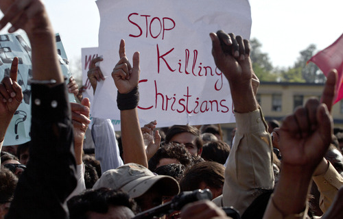 Pakistani Christians raise their hands during a demonstration demanding that the government rebuild their homes after they were burned down following an alleged blasphemy incident, in Islamabad, Pakistan, Sunday, March 10, 2013. The incident in Lahore began on Friday, March 8, 2013 after a Muslim accused a Christian man of blasphemy, an offence that in Pakistan is punished by life in prison or death. (AP Photo/Anjum Naveed)