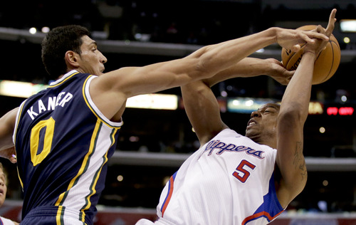Utah Jazz center Enes Kanter, left, fouls Los Angeles Clippers forward Caron Butler during the second half of an NBA basketball game in Los Angeles, Saturday, Feb. 23, 2013. (AP Photo/Chris Carlson)