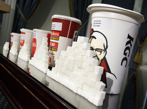 FILE - This May 31, 2012 file photo shows a display of various size cups and sugar cubes at a news conference at New York's City Hall. A judge struck down New York City's groundbreaking limit on the size of sugar-laden drinks Monday, March 11, 2013 shortly before it was set to take effect, agreeing with the beverage industry and other opponents that the rule is arbitrary in applying to only some sweet beverages and some places that sell them. (AP Photo/Richard Drew, File)