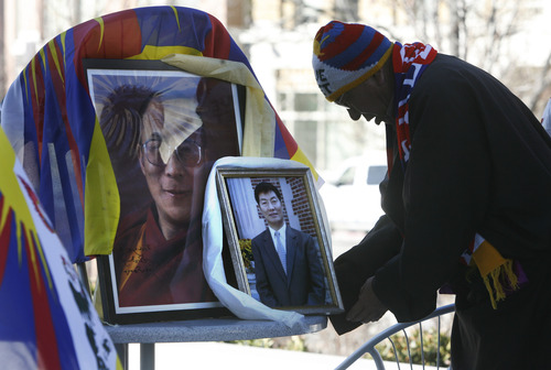 Scott Sommerdorf  |  The Salt Lake Tribune A man from the Tibetan community of Utah places a photo of Tibet's Prime Minister Lobsang Sangay next to a photo of the Dalai Lama, as the community observed the 54th worldwide commemoration of National Tibetan Uprising Day at the Wallace Bennett Federal Building, Sunday, March 10, 2013. On this date in 1959, tens of thousands of Tibetans took to the streets of Lhasa, Tibet's capital, rising up against China's illegal invasion and occupation of their homeland.