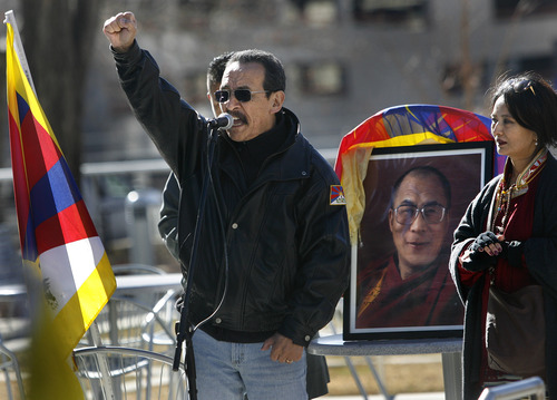 Scott Sommerdorf  |  The Salt Lake Tribune Jamyang Norbu, a Tibetan political activist and writer, speaks next to a portrait of the Dalai Lama during the observance of the 54th worldwide commemoration of National Tibetan Uprising Day at the Wallace Bennett Federal Building, Sunday, March 10, 2013.  On this date in 1959, tens of thousands of Tibetans took to the streets of Lhasa, Tibet's capital, rising up against China's illegal invasion and occupation of their homeland.