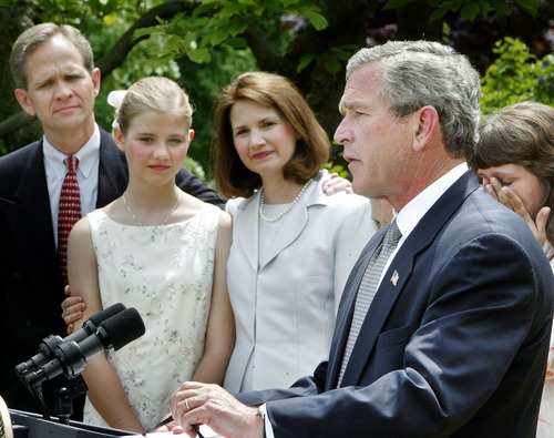 President Bush speaks before signing a wide-ranging package of child safety measures  in the  Rose Garden of the White House Wednesday, April 30, 2003, in Washington. With Bush on stage are the Smart family, left to right, Ed Smart, Elizabeth Smart, and Lois Smart. Elizabeth was recently reunited with her family after being kidnapped. Woman at right is Donna Norris.     (AP Photo/Ron Edmonds)