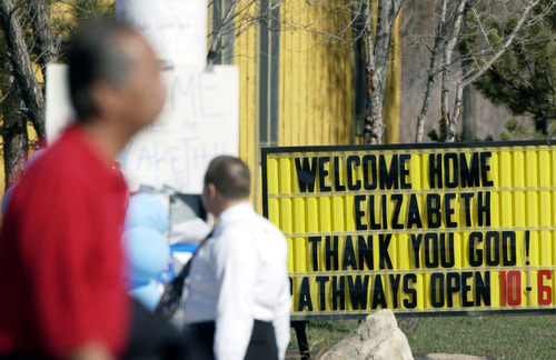 Steve Griffin  |  The Salt Lake Tribune  A sign near the corner where Elizabeth Smart was found in Sandy welcome's her home as pedestrians pass by the corner of 10200 south State Street March 13, 2003.