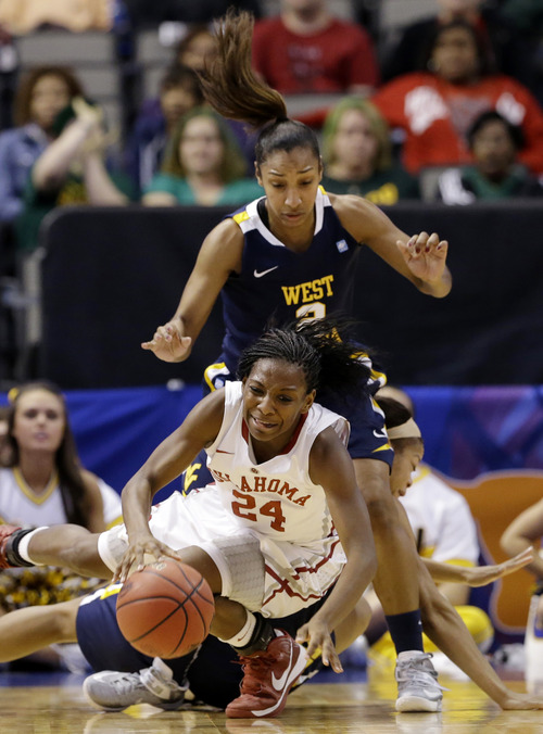 Oklahoma's Sharane Campbell (24) maintains control of the ball as she is knocked down by West Virginia' Christal Caldwell, bottom rear, as Taylor Palmer (2) watches in the first half of an NCAA college basketball game at the Big 12 Conference women's tournament Saturday, March 9, 2013, in Dallas. (AP Photo/Tony Gutierrez)
