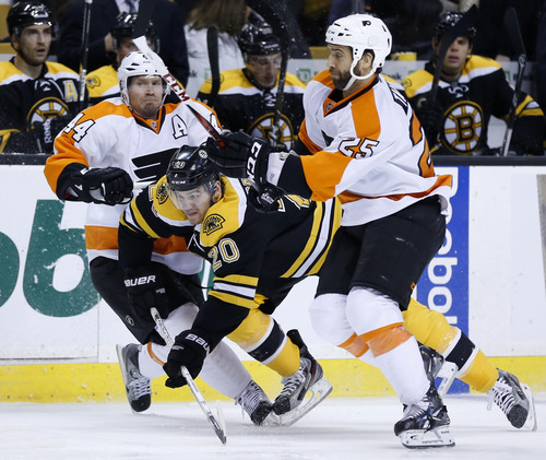 Boston Bruins' Daniel Paille (20) skates between Philadelphia Flyers' Kimmo Timonen, left, of Finland, and Maxime Talbot (25) in the second period of an NHL hockey game in Boston, Saturday, March 9, 2013. (AP Photo/Michael Dwyer)