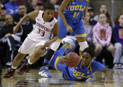 Stanford's Amber Orrange, left, moves toward the ball as UCLA's Jasmine Dixon tries to keep control of it during the first half of an NCAA college basketball game in the championship of the Pac-12 Conference tournament, Sunday, March 10, 2013, in Seattle. (AP Photo/Elaine Thompson)
