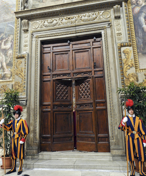 """In this picture released by the Vatican newspaper L'Osservatore Romano, Monsignor Guido Marini, Master of Liturgical Ceremonies, partly seen behind the doors, closes the double doors to the Sistine Chapel in after shouting """"Extra omnes,"""" Latin for """"all out,"""" telling everyone but those taking part in the conclave to leave the frescoed hall, at the Vatican, Tuesday, March 12, 2013. Marini then locked the doors. Cardinals from around the globe locked themselves inside the Sistine Chapel on Tuesday to choose a new leader for the world's 1.2 billion Catholics and their troubled church, surrounded by Michelangelo's imposing frescos imagining the beginning and the end of the world. (AP Photo/L'Osservatore Romano, ho)"""