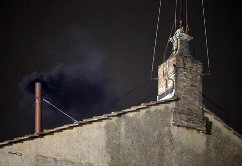 Black smoke emerges from the chimney on the roof of the Sistine Chapel, in St. Peter's Square at the Vatican, Tuesday, March 12, 2013. The black smoke indicates that the new pope has not been elected yet. (AP Photo/Gregorio Borgia)