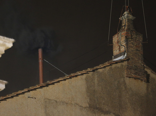 smoke emerges from the chimney on the roof of the Sistine Chapel, in St. Peter's Square at the Vatican, Tuesday, March 12, 2013. The black smoke indicates that the cardinals did not elect a new pope. (AP Photo/Dmitry Lovetsky)
