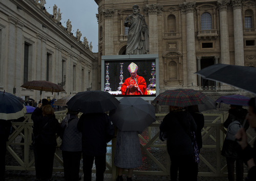 Faithful hold their umbrellas as they follow a mass inside St. Peter's Basilica celebrated by Cardinal Angelo Sodano, seen on a giant screen in St. Peter's Square, Tuesday, March 12, 2013. Cardinals enter the Sistine Chapel on Tuesday to elect the next pope amid more upheaval and uncertainty than the Catholic Church has seen in decades: There's no front-runner, no indication how long voting will last and no sense that a single man has what it takes to fix the many problems. (AP Photo/Emilio Morenatti)