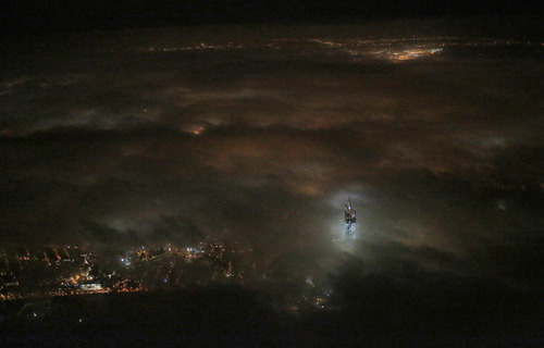 One World Trade Center emerges from the clouds in the night sky in a photo made from a passing airplane, Monday, March 11, 2013 in New York. Construction continues on the office complex going up on the site of the original World Trade Center, which was destroyed in the terrorist attacks of Sept. 11, 2001. (AP Photo/Matthew Ziegler)