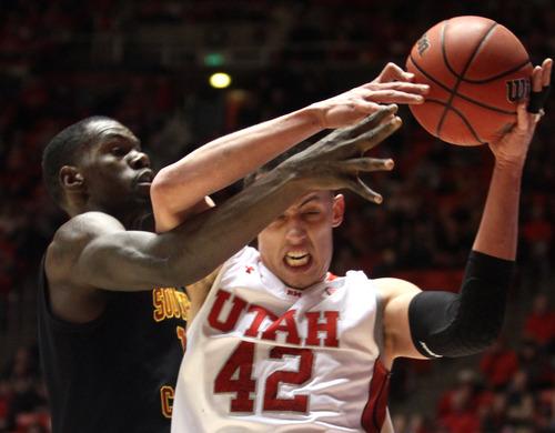 Rick Egan  | The Salt Lake Tribune   Utah center Jason Washburn (42) wrestles the ball from USC forward Dewayne Dedmon (14) during a game at the Huntsman Center in Salt Lake City on Saturday, Jan. 12, 2013.