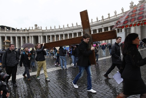 Pilgrims carry a cross through St. Peter's Square while cardinals meet in conclave in the Sistine Chapel to elect a new pope at the Vatican, Wednesday, March 13, 2013. (AP Photo/Andrew Medichini)