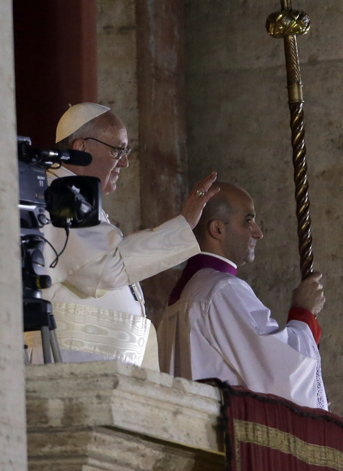Pope Francis waves to the crowd from the central balcony of St. Peter's Basilica at the Vatican, Wednesday, March 13, 2013. Cardinal Jorge Bergoglio who chose the name of  Francis is the 266th pontiff of the Roman Catholic Church.  (AP Photo/Luca Bruno)