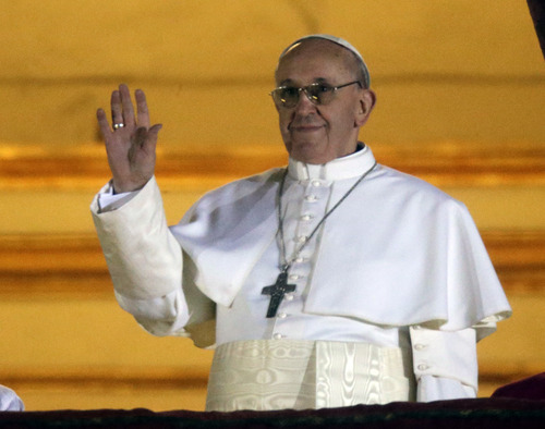Pope Francis waves to the crowd from the central balcony of St. Peter's Basilica at the Vatican, Wednesday, March 13, 2013. Cardinal Jorge Bergoglio who chose the name of  Francis is the 266th pontiff of the Roman Catholic Church. (AP Photo/Gregorio Borgia)