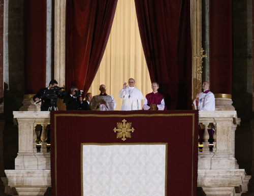 Pope Francis flanked by Monsignor Guido Marini, master of liturgical ceremonies, waves to the crowd from the central balcony of St. Peter's Basilica at the Vatican, Wednesday, March 13, 2013. Cardinal Jorge Bergoglio, who chose the name of Francis is the 266th pontiff of the Roman Catholic Church. (AP Photo/Michael Sohn)