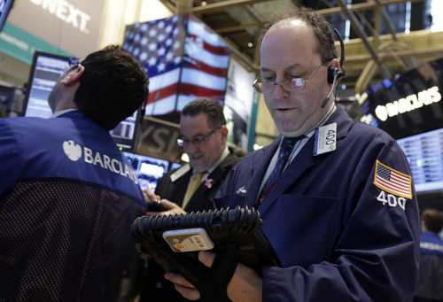 FILE -In this Tuesday, Feb. 26, 2013, file photo, Trader Gordon Charlop, right, works on the floor of the New York Stock Exchange. World stock markets shared Wall Street's ebullience and turned higher Thursday March 14, 2013 ahead of the release of U.S. jobless claims. (AP Photo/Richard Drew, File)