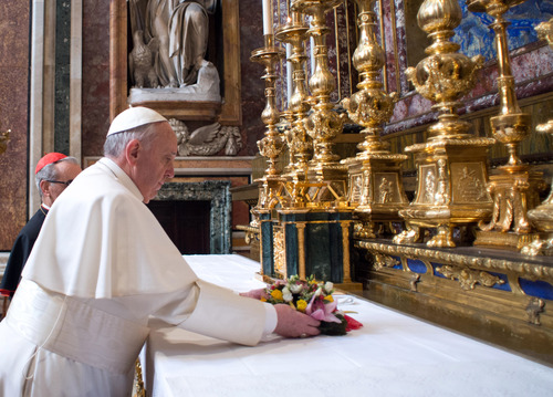 In this photo provided by the Vatican newspaper L'Osservatore Romano, Pope Francis puts flowers on the altar inside St. Mary Major Basilica, in Rome, Thursday, March 14, 2013. Pope Francis opened his first morning as pontiff by praying Thursday at Rome's main basilica dedicated to the Virgin Mary, a day after cardinals elected him the first pope from the Americas in a bid to revive a Catholic Church in crisis and give it a preacher with a humble touch. (AP Photo/L'Osservatore Romano, ho)