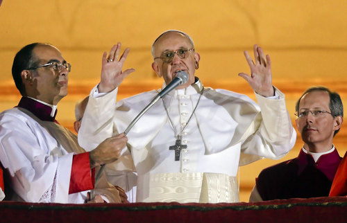 Pope Francis waves to the crowd from the central balcony of St. Peter's Basilica at the Vatican, Wednesday, March 13, 2013. Cardinal Jorge Bergoglio who chose the name of  Francis, is the 266th pontiff of the Roman Catholic Church. (AP Photo/Gregorio Borgia)