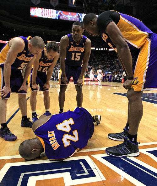 Los Angeles Lakers' Steve Blake, from left, Steve Nash, Metta World Peace and Dwight Howard gather around Kobe Bryant as he lays on the floor after being injured in the final seconds of an NBA basketball game against the Atlanta Hawks on Wednesday, March 13, 2013, in Atlanta. The Hawks defeated the Lakers 96-92.  (AP Photo/Atlanta Journal-Constitution, Curtis Compton)