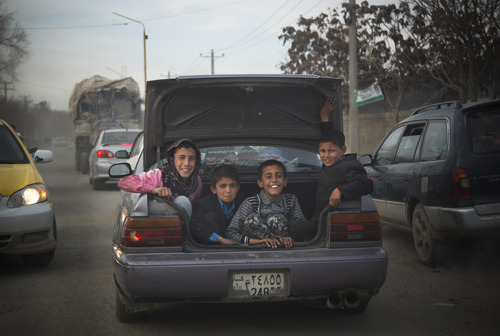 Afghan boys peer out from the trunk of a car as they get a ride through the center of Kabul, Friday, March 15, 2013. (AP Photo/Anja Niedringhaus)