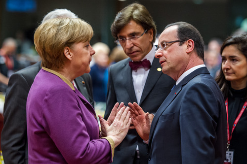 German Chancellor Angela Merkel, second left, speaks with French President Francois Hollande, second right, during a round table meeting at an EU summit in Brussels on Friday, March 15, 2013. On the second anniversary of an uprising that evolved into Syria's brutal civil war, the European Union's national leaders will likely discuss whether to arm rebels trying to overthrow the regime of Bashar Assad. (AP Photo/Geert Vanden Wijngaert)