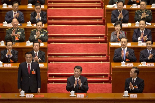 Newly-named Chinese Premier Li Keqiang stands up when he was announced to be the nation's new premier, while Chinese President Xi Jinping, center, and former Chinese Premier Wen Jiabao, front right, clap with delegates and other top Chinese leaders during a plenary session of the National People's Congress held in Beijing's Great Hall of the People Friday, March 15, 2013. (AP Photo/Alexander F. Yuan)