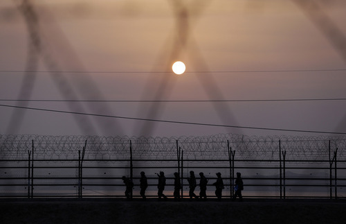 South Korean army soldiers patrol along a barbed-wire fence at sunset near the border village of Panmunjom, which has separated the two Koreas since the Korean War, in Paju, north of Seoul, South Korea, Friday, March 15, 2013. Busloads of tourists still show up to gawk at the world's most heavily fortified border, even as governments on both sides threaten to reduce each other to rubble. (AP Photo/Lee Jin-man)