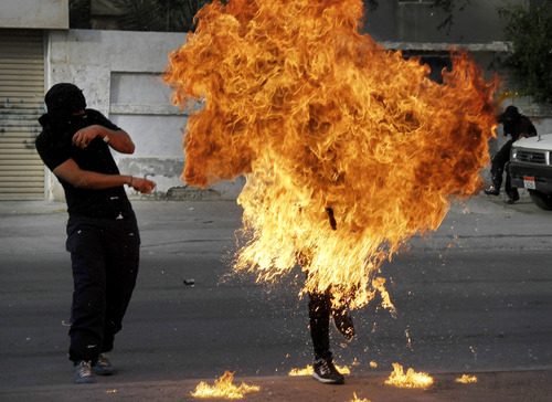 "A Bahraini anti-government protester is engulfed in flames when a shot fired by riot police hit the petrol bomb in his hand that he was preparing to throw during clashes in Sanabis, Bahrain, Thursday, March 14, 2013. Protests and clashes erupted in opposition areas nationwide Thursday with government opponents observing a ""Dignity Strike"" blocking roads, closing shops, protesting and staying home from work and school called by the more radical February 14 youth group. (AP Photo/Hasan Jamali)"