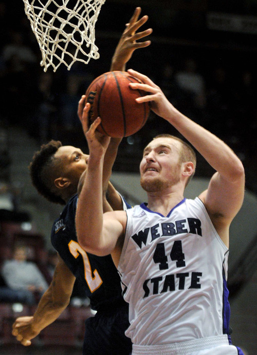 Weber State's Kyle Tresnak (44) heads to the basket against Northern Arizona's Michael Dunn during their NCAA college basketball game in the Big Sky Conference tournament, Thursday, March 14, 2013, in Missoula, Mont. Weber State won 84-58. (AP Photo/The Missoulian, Michael Gallacher)  MAGS OUT; TV OUT