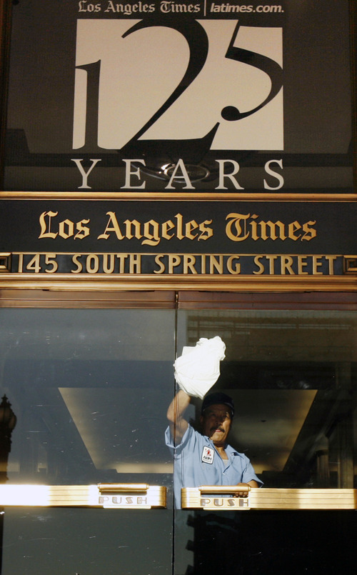 """FILE - In this Nov. 16, 2006 file photo, a worker cleans an entrance to the Los Angeles Times building in Los Angeles.   Federal authorities allege that Matthew Keys provided hackers with login information to access the Tribune Company's computer system in December 2010. Keys had been fired months before from a Sacramento television station owned by Tribune. Keys was a web producer for KTXL. Tribune also owns the Times. The investigators allege that Keys gave a hacker named """"Sharpie"""" the information in an Internet chat room frequented by hackers and urged the hacker to do some damage to the Tribune company. (AP Photo/Ric Francis)"""
