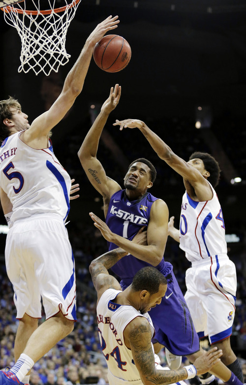 Kansas center Jeff Withey (5), forward Kevin Young (40) and guard Travis Releford (24) block a shot by Kansas State guard Shane Southwell (1) during the first half of the championship NCAA college basketball game of the Big 12 tournament, Saturday, March 16, 2013, in Kansas City, Mo. (AP Photo/Charlie Riedel)