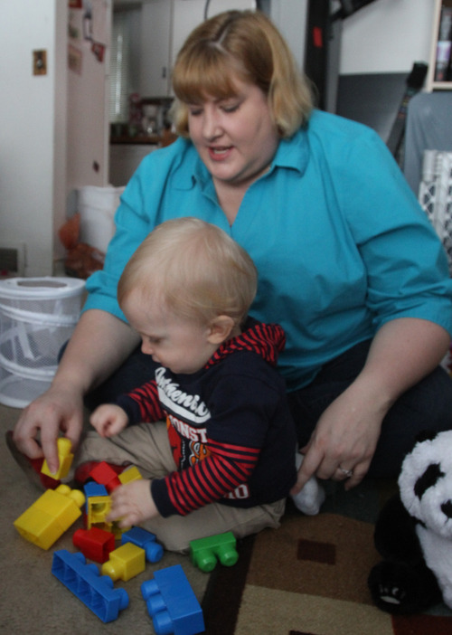 Rick Egan  | The Salt Lake Tribune   Jacy Morgan-Barnum's plays with her son Bradley, in their home in Ogden, Saturday, February 23, 2013. Jacy Morgan-Barnum's insurance company refused to cover a corrective helmet prescribed to correct a flat spot on her Bradley's head, she took action.