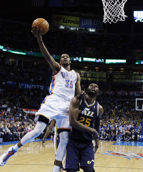 Jazz center Al Jefferson, here giving up a basket to Oklahoma City Thunder forward Kevin Durant, had been criticized for his defensive shortcomings. But Utah coach Ty Corbin says the Jazz's defensive issues are bigger than Jefferson.  (AP Photo/Sue Ogrocki)