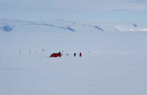 """In this Sunday, Jan. 20, 2013 photo, cross-country skiers pass a survival shelter on Hut Point Peninsula of Ross Island, Antarctica. Tourism is rebounding here five years after the financial crisis stifled what had been a burgeoning industry. And it's not just retirees watching penguins from the deck of a ship. Visitors are taking tours inland and even engaging in """"adventure tourism"""" like skydiving and scuba diving under the ever-sunlit skies of a Southern Hemisphere summer. (AP Photo/Rod McGuirk)"""