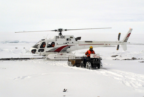 """In this Sunday, Jan. 20, 2013 photo, a sightseeing helicopter lands near New Zealand's Scott Base on Ross Island, Antarctica. Tourism is rebounding here five years after the financial crisis stifled what had been a burgeoning industry. And it's not just retirees watching penguins from the deck of a ship. Visitors are taking tours inland and even engaging in """"adventure tourism"""" like skydiving and scuba diving under the ever-sunlit skies of a Southern Hemisphere summer. (AP Photo/Rod McGuirk)"""