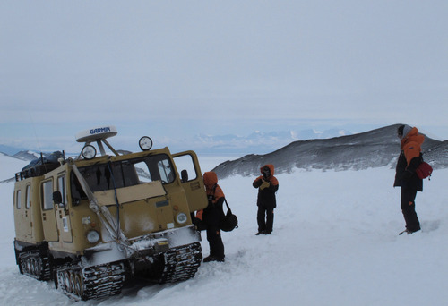 """In this Sunday, Jan. 20, 2013 photo, sightseers board an over-snow vehicle on Hut Point Peninsula of Ross Island in Antarctica. Tourism in Antarctica is rebounding five years after the financial crisis stifled what had been a burgeoning industry. Tourism is rebounding here five years after the financial crisis stifled what had been a burgeoning industry. And it's not just retirees watching penguins from the deck of a ship. Visitors are taking tours inland and even engaging in """"adventure tourism"""" like skydiving and scuba diving under the ever-sunlit skies of a Southern Hemisphere summer.  (AP Photo/Rod McGuirk)"""