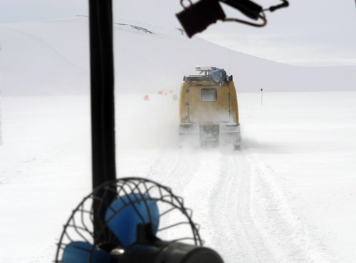 """In this Sunday, Jan. 20, 2013 photo, a Hagglunds over-snow vehicle is photographed from a similar vehicle traveling in convoy on a sightseeing journey along Hut Point Peninsula of Ross Island, Antarctica. Tourism is rebounding here five years after the financial crisis stifled what had been a burgeoning industry. And it's not just retirees watching penguins from the deck of a ship. Visitors are taking tours inland and even engaging in """"adventure tourism"""" like skydiving and scuba diving under the ever-sunlit skies of a Southern Hemisphere summer. (AP Photo/Rod McGuirk)"""