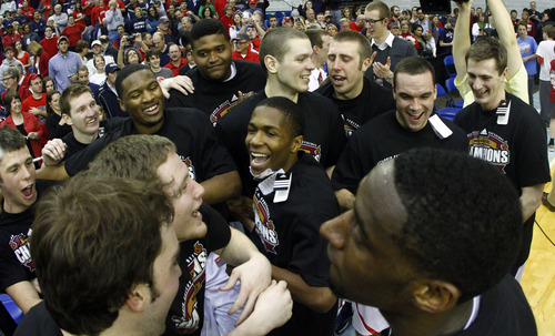 Belmont guard Kerron Johnson, center, celebrates with teammates after an NCAA college basketball game against Murray State in the Ohio Valley Conference tournament championship on Saturday, March 9, 2013, in Nashville, Tenn. Johnson made the game-winning basket in their 70-68 win in overtime. (AP Photo/Wade Payne)