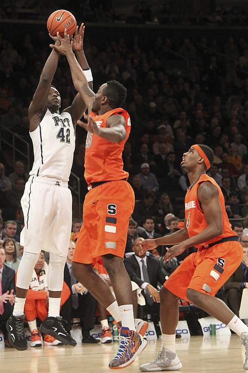 Pittsburgh's Talib Zanna (42) goes up past Syracuse's Rakeem Christmas (25) and C.J. Fair during the first half of an NCAA college basketball game at the Big East Conference tournament, Thursday, March 14, 2013 in New York. (AP Photo/Mary Altaffer)