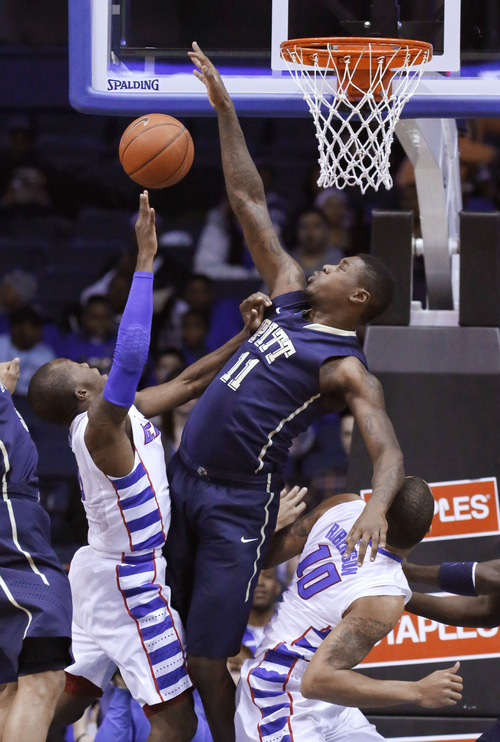 Pittsburgh forward Dante Taylor (11) blocks the shot of DePaul guard Worrel Clahar (0) as Derrell Robertson Jr. (10) is blocked out during the first half of an NCAA college basketball game Saturday, March 9, 2013, in Rosemont, Ill. (AP Photo/Charles Rex Arbogast)