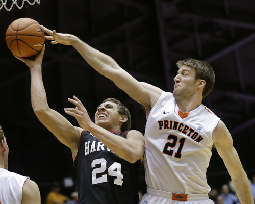 Harvard's Jonah Travis (24) takes a shot past Princeton's Mack Darrow (21) during the first half of an NCAA college basketball game Friday, March 1, 2013, in Princeton, N.J. (AP Photo/Mel Evans)
