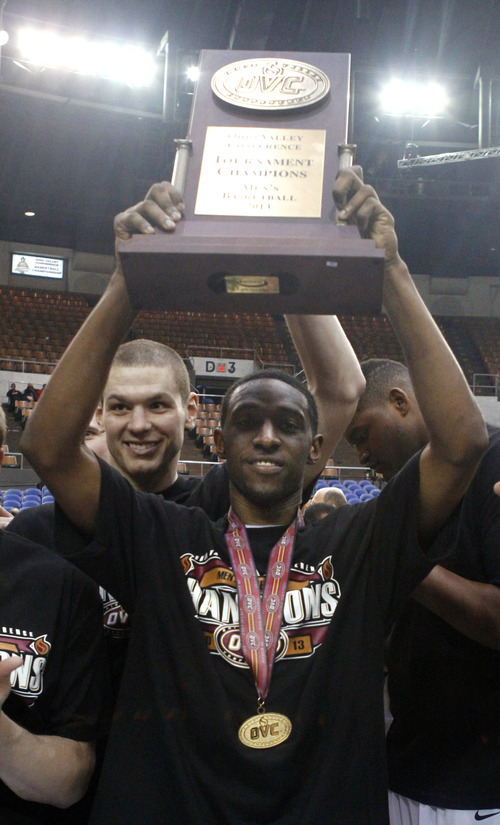Belmont guard Ian Clark holds up the trophy after an NCAA college basketball game against Murray State for the Ohio Valley Conference men's tournament championship  Saturday, March 9, 2013, in Nashville, Tenn. Belmont won in overtime, 70-68. (AP Photo/Wade Payne)
