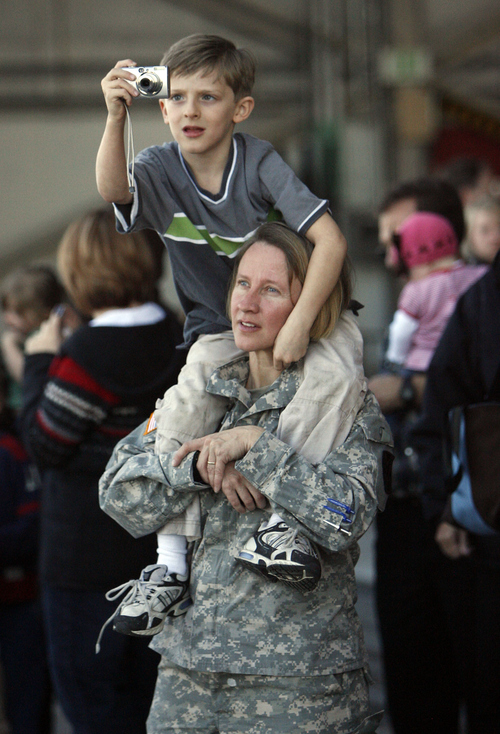 Francisco Kjolseth | The Salt Lake Tribune   Waiting for the second wave of deployment later that day, Annette Aldridge of the 142nd, hoists her son Isaac, 6, as he looks for a better shot.  Members of the 142nd Military Intelligence Battalion, the first Utah National Guard unit to take a second combat tour, said goodbye to loved ones  at the Guard base hangar in Salt Lake City February 26, 2008.