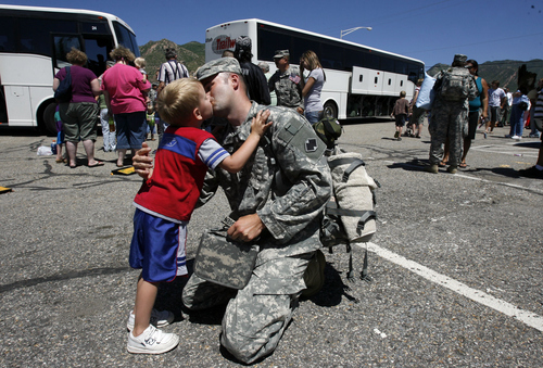 Salt Lake City - Heber Rasmussen gets a good bye kiss from his son Isaac, 4, as he joins 340 soldiers for the latest deployment. The 96th Sustainment Brigade from Fort Douglas loaded up on buses for a one year deployment to Iraq after completing training in Fort Hood TX.  Photo by Francisco Kjolseth/The Salt Lake Tribune 7/08/2009