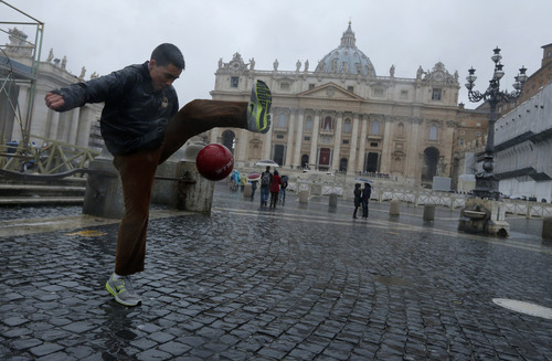 A boy plays football in St. Peter's Square at the Vatican, Monday, March 18, 2013. The Vatican is releasing details of the pope's installation Mass on Tuesday as well images of his coat of arms and fisherman's ring. In addition to more than 132 government delegations, the Vatican said 33 Christian delegations will be present, as well as representatives from Jewish, Muslim, Buddhist, Sikh and Jain communities. (AP Photo/Dmitry Lovetsky)