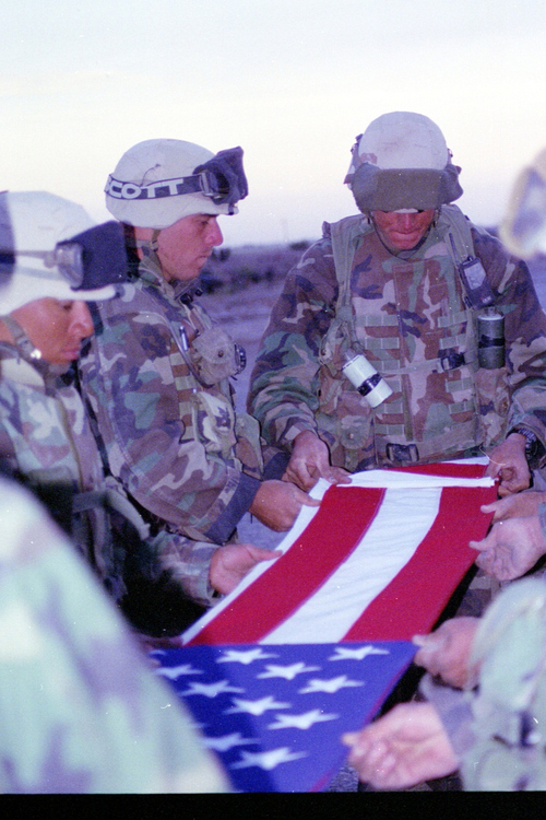 Sgt. Spencer (right) and Cpl. Stroh fold a flag at the memorial service for Staff Sgt. James Cawley, a member of Fox Company, 2nd Battalion, 23rd Marines, who died in an accident on the way to Baghdad.